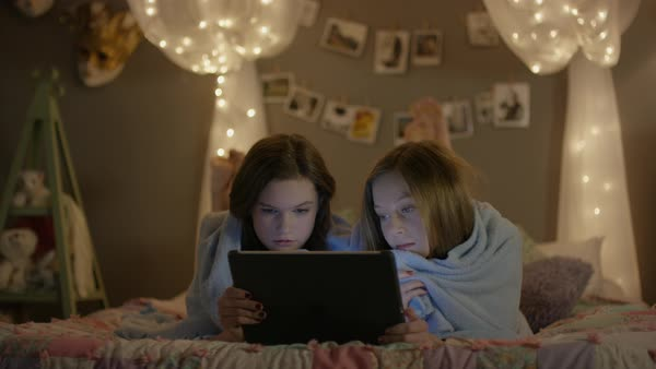 Medium shot of teenage girls watching scary movie at sleepover Royalty-free stock video
