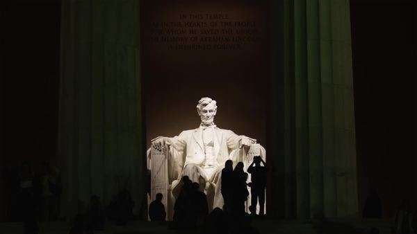 WS Silhouettes of people in front of Abraham Lincoln statue at Lincoln Memorial illuminated at night, Washington D.C Royalty-free stock video