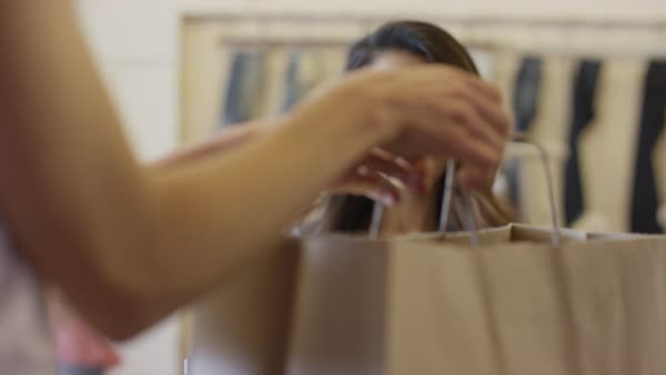 Close up shot of cashier bagging clothing for customer in store Royalty-free stock video