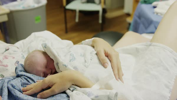 Close up shot of mother holding newborn baby daughter in hospital Rights-managed stock video
