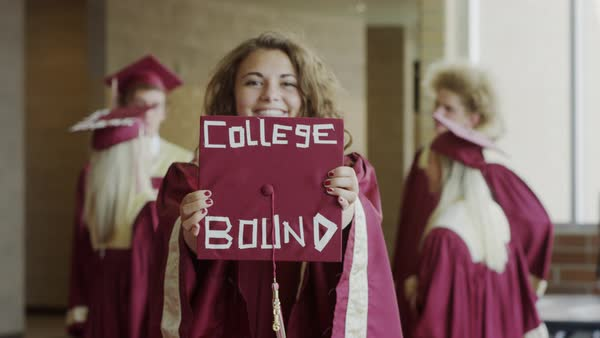 Medium shot of graduate showing mortarboard with message in corridor Rights-managed stock video