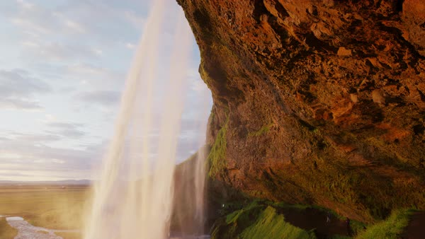 Wide slow motion crane shot of waterfall pouring over cliff Rights-managed stock video