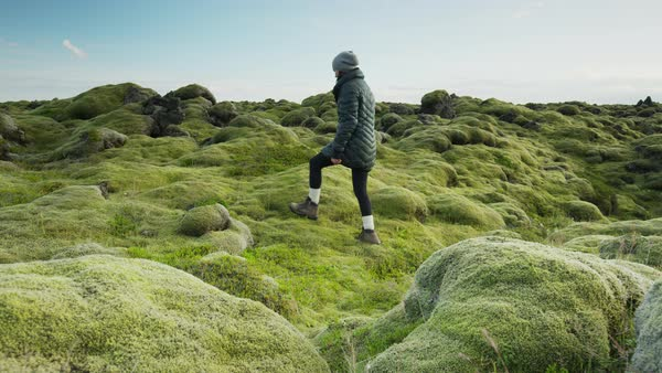 Wide slow motion panning shot of woman walking then laying in mossy landscape Rights-managed stock video