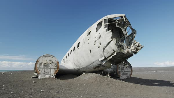 Wide panning shot of airplane wreckage in remote landscape Royalty-free stock video