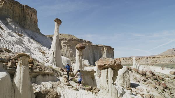 Wide panning shot of people hiking on unusual rock formations Royalty-free stock video
