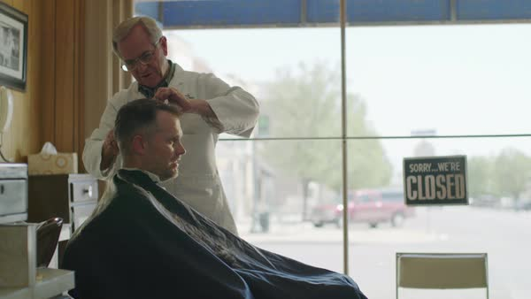 Medium shot of barber cutting hair of customer Royalty-free stock video