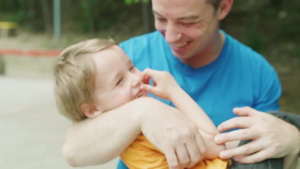 Close-up slow motion shot of father cradling son in park / Plovdiv, Bulgaria Royalty-free stock video