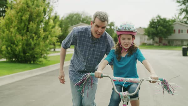 Medium tracking shot of father teaching daughter to ride bicycle Rights-managed stock video