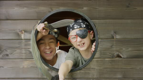 Close up of fierce boys playing pirate in window with swords / Provo, Utah, United States Royalty-free stock video