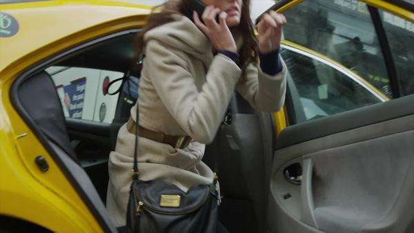 Close up panning shot of young woman on cell phone getting out of taxi / New York City, New York, United States Royalty-free stock video