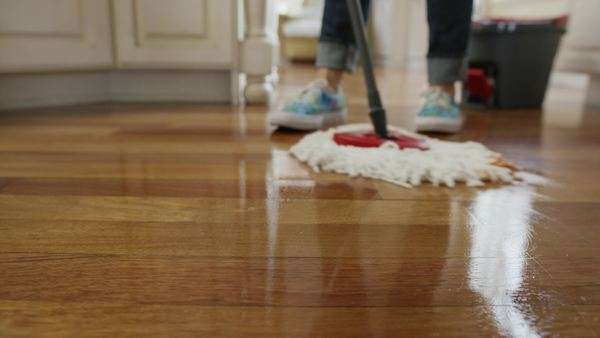 Low angle medium panning shot of woman mopping kitchen floor - Stock ...