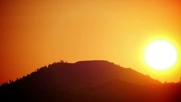 Large sun rising in a red sky over a hill. telephoto timelapse. Royalty-free stock video