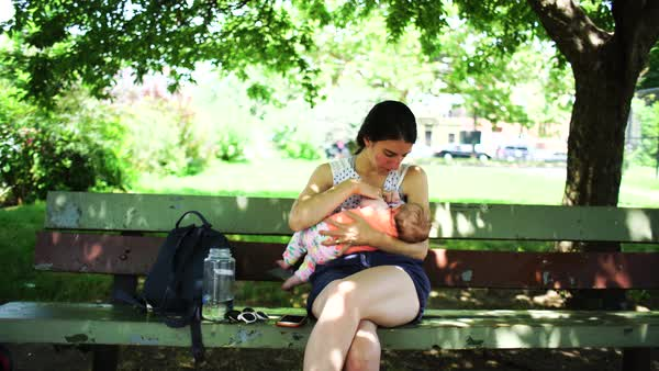 Medium shot of a woman breastfeeding her baby on a bench Royalty-free stock video