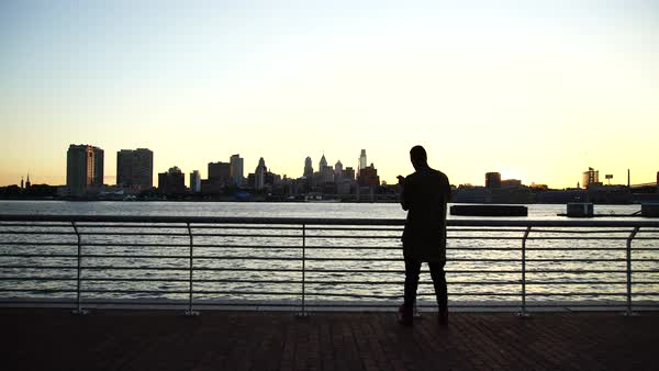 Medium wide shot of a man standing on a pier in Philadelphia, PA, USA Royalty-free stock video