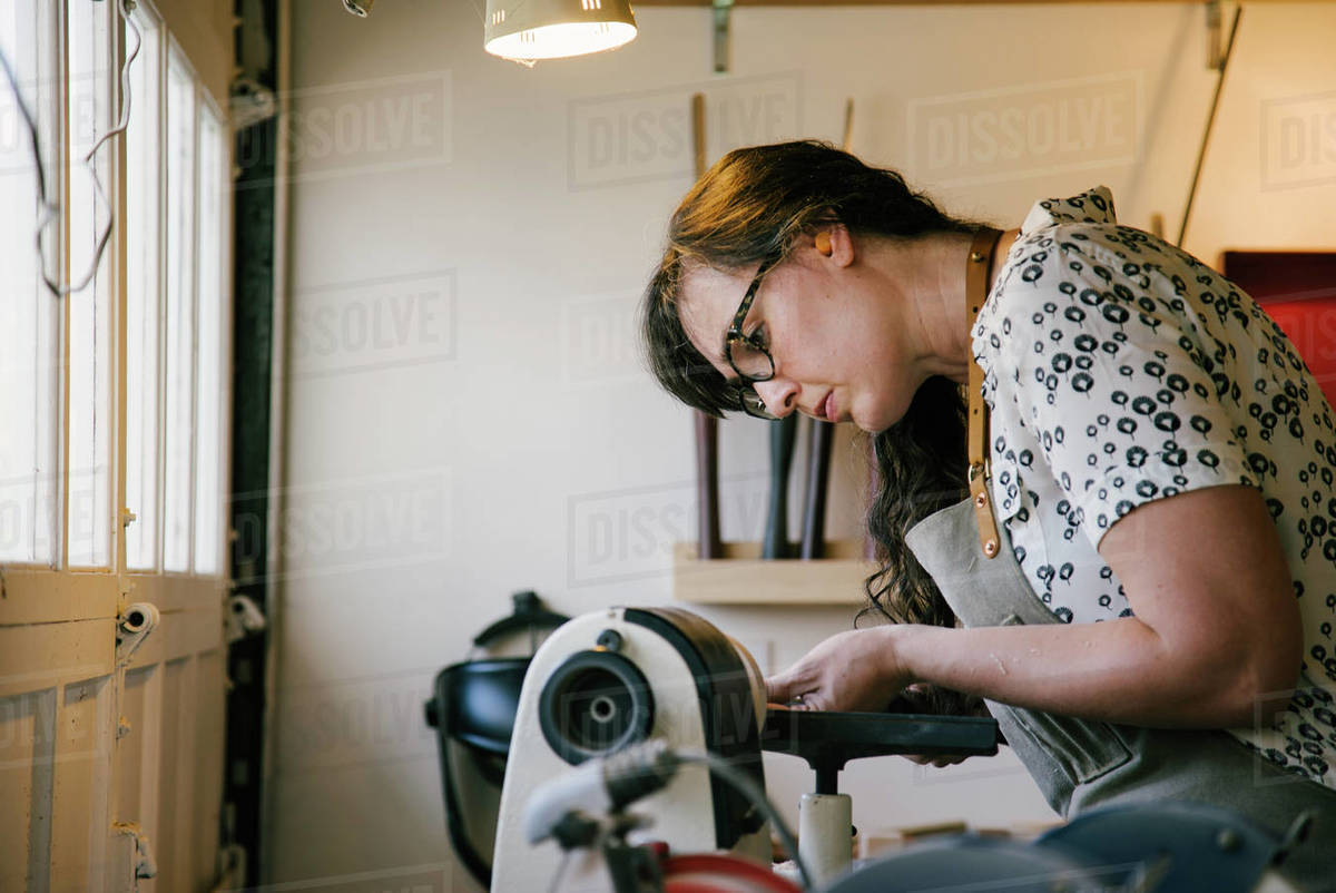 Female carpenter working on woodworking machinery in workshop Royalty-free stock photo