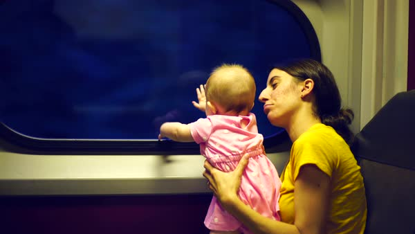 Hand-held close-up of mother and baby traveling by train Royalty-free stock video