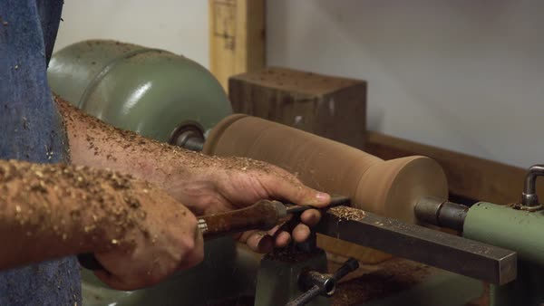 Hand-held shot of a man shaping a piece of wood with a lathe Royalty-free stock video