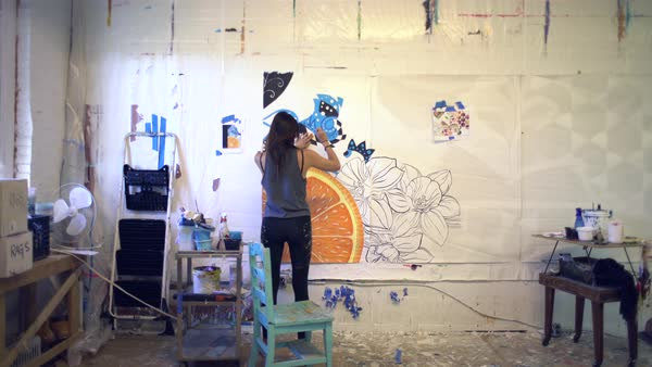 Back view of a woman painting in a studio Royalty-free stock video