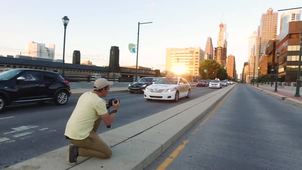Gimbal shot of a man taking photographs of traffic at sunset Royalty-free stock video