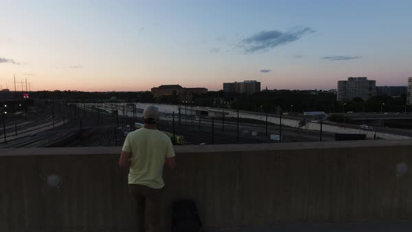 Tracking shot of a man taking photographs of traffic from a rooftop Royalty-free stock video