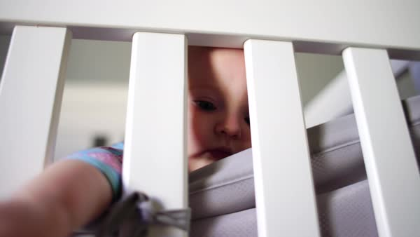 Hand-held shot of a baby reaching out of a crib Royalty-free stock video