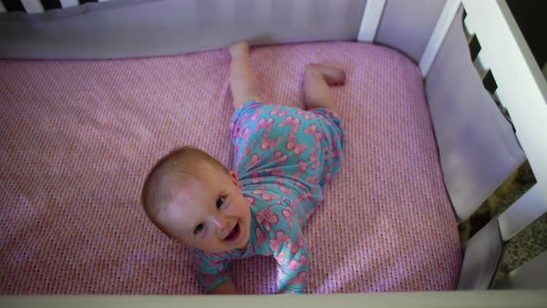 High-angle shot of a baby rolling over in a crib Royalty-free stock video