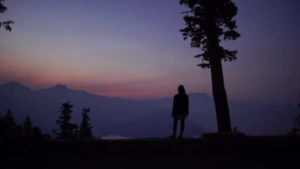 Moving shot of woman looking at mountain landscape at sunset at Crater Lake, Oregon Rights-managed stock video
