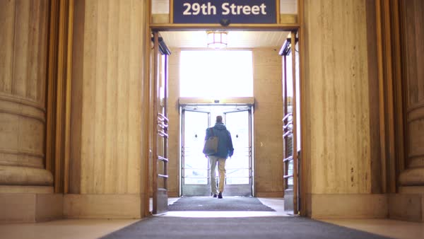 Wide shot of a man exiting the 30th Street Station in Philadelphia Rights-managed stock video