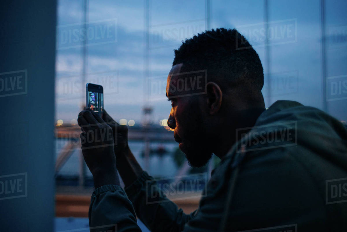 Close-up shot of a man taking a picture with a smartphone while standing outdoors at dusk Royalty-free stock photo