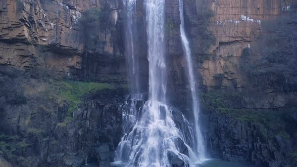 Waterfall revealed from bottom to top of gorge over rural african road Royalty-free stock video