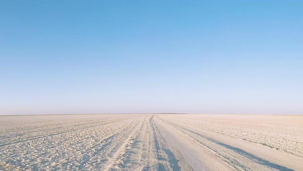 Low angle shot of barren road on salt pan with tracks criss crossing into the distance Royalty-free stock video