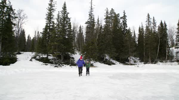Mother with son ice skating on frozen lake Royalty-free stock video
