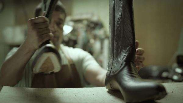 4k Man placing hand crafted cowboy boots on shelf, slow dolly Royalty-free stock video