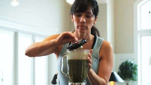 Woman in the kitchen making a green smoothie in the blender Royalty-free stock video