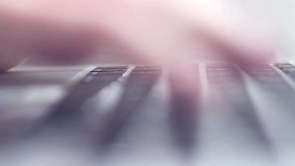Macro shot of young woman hands typing on a laptop keyboard, low-contrast backlit with shallow depth of field Royalty-free stock video