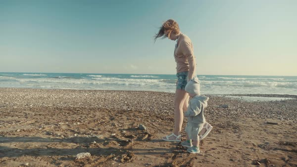 Caring young mother and little cute son holding hands walk slow steps along the empty shoreline near the sea in windy weather Royalty-free stock video