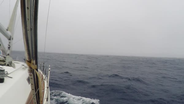 POV yacht with sails lowered floats over the stormy sea, ocean at high speed. Splashes of water, gloomy weather. Sea view through the deck of the yacht Royalty-free stock video