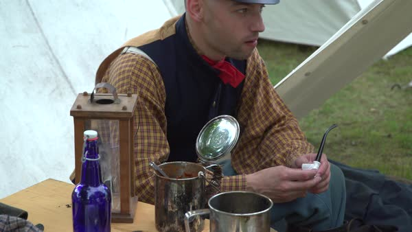 View of Civil War soldier preps his tobacco pipe Royalty-free stock video