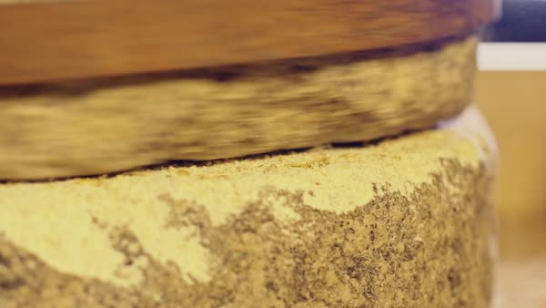 Close-up shot of historic hand-driven millstone grinding wheat Royalty-free stock video