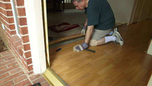A workman or homeowner handyman type engaged in a DIY project of removing old laminate flooring in preparation of new floor covering. Royalty-free stock video