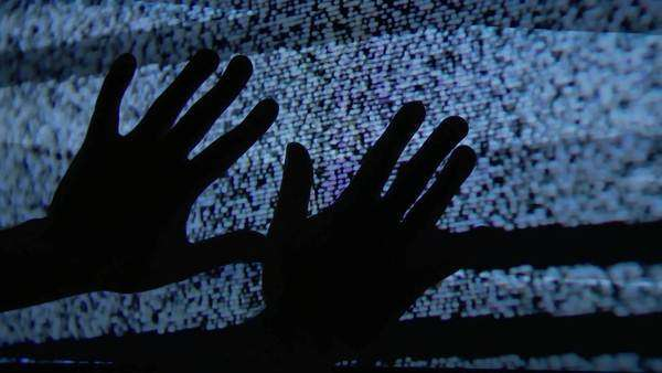 A mysterious set of hands touch the static on a television screen. Royalty-free stock video