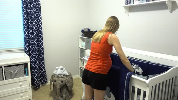 A young pregnant woman places a blanket on the crib in her new nursery.  	 Royalty-free stock video