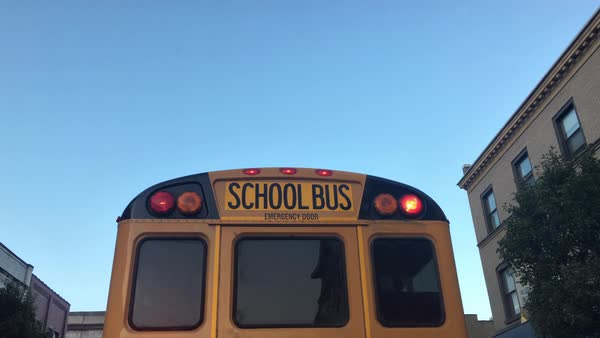 Following a school bus in the early morning in a small town as it stops to pick up children.  	 Royalty-free stock video