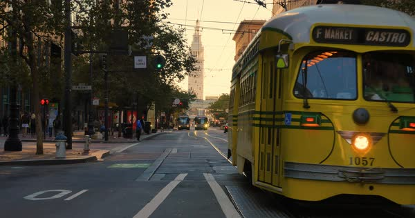 SAN FRANCISCO - Circa October, 2016 - A yellow streetcar travels on Market Street with the Port of San Francisco Ferry Building in the Distance. Royalty-free stock video