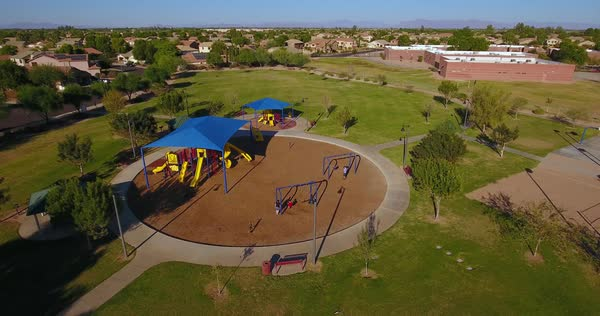 A daytime aerial establishing shot of a typical Arizona neighborhood playground and park.  	 Royalty-free stock video