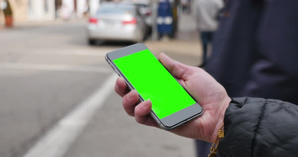 A woman holding a green screen smartphone in a city 	 Royalty-free stock video
