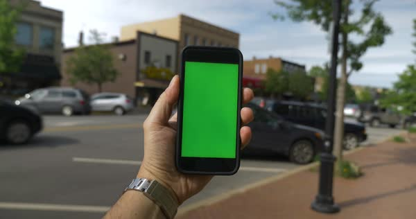 A person's perspective walking in the business district in a small town while holding a green screen smartphone. Royalty-free stock video