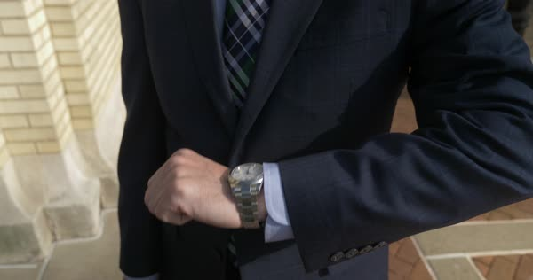 A businessman checks his watch for the time while walking downtown. Royalty-free stock video
