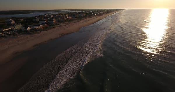 An early morning forward aerial establishing shot of the houses along Topsail Island on the Atlantic Ocean in North Carolina.  Royalty-free stock video