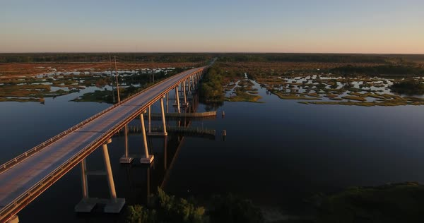 An early morning sunrise reverse aerial establishing shot of the Topsail Island Bridge over the Intracoastal Waterway.  Royalty-free stock video